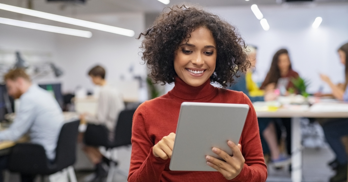 Happy coworking space operator using office automation software to easily manage her workspace.